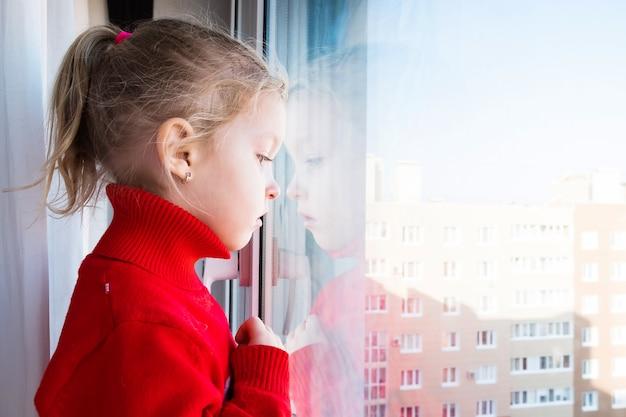 La bambina molto triste e scontrosa sta guardando fuori dalla finestra. quarantena pandemica. resta a casa. covid-19 lockdown e bambini.