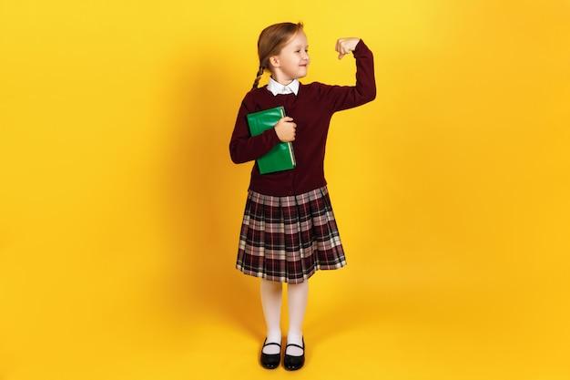 La bambina mostra la forza della mano e tiene un libro.