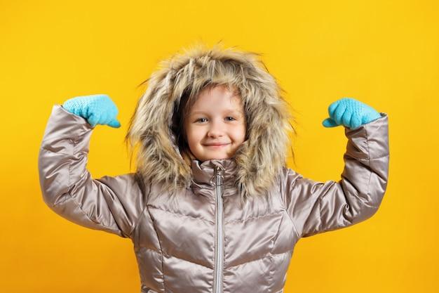 La bambina mostra le mani forti.