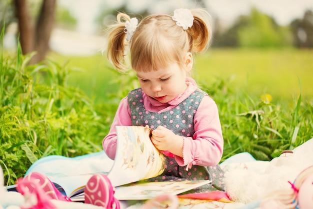 La bambina nel parco di primavera legge il libro nella calda giornata
