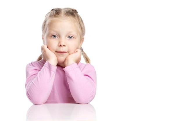 La bambina pensierosa con le trecce si siede a un tavolo e sogna.