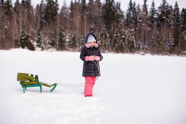 La bambina porta il suo giro in slitta sulla neve