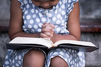 La bambina prega con una sacra bibbia