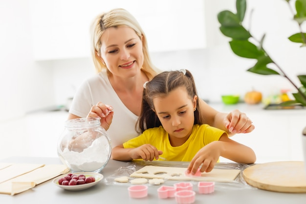 La bambina produce i biscotti dall'impasto nella cucina a casa