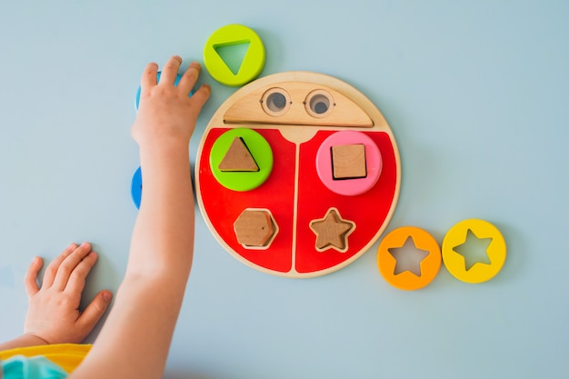 La bambina raccoglie il selezionatore multicolore di legno giocattoli per bambini di legno naturali sicuri
