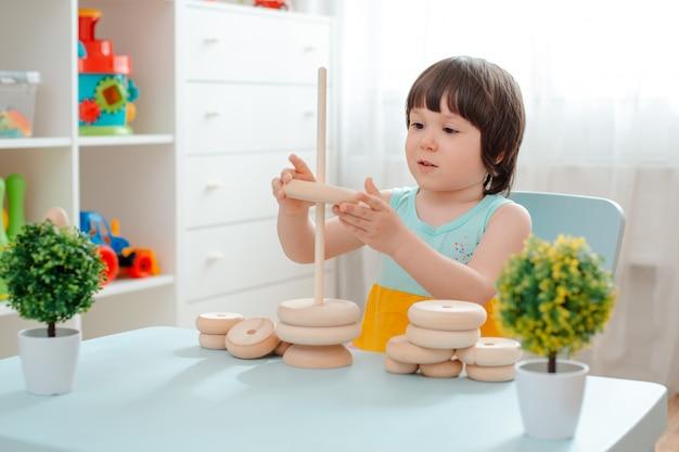 La bambina raccoglie una piramide di legno non dipinta. giocattoli per bambini in legno naturale sicuri.