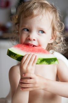 La bambina riccia con piacere mangia una fetta di anguria in estate