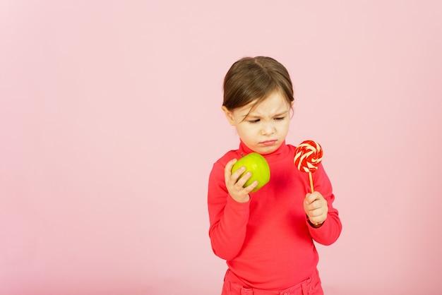 La bambina sceglie tra una lecca-lecca e una mela verde. il concetto di corretta alimentazione. un bambino in una parete rosa tiene in mano un dolce di zucchero e una mela. difficoltà di scelta