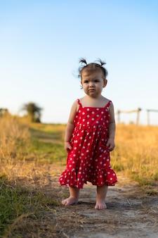 La bambina si diverte nel prato, correndo a piedi nudi sull'erba.