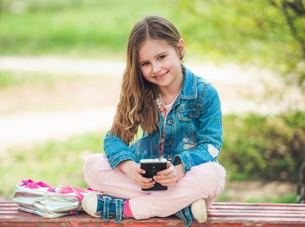La bambina si siede con il suo telefono nel parco