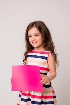 La bambina sorride e tiene una pagina rosa