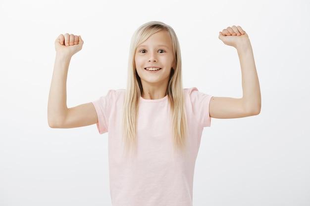 La bambina sorridente allegra alza le mani, vincendo e trionfando