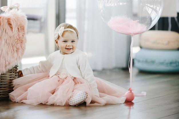 La bambina sorridente in un affascinante vestito rosa si siede sul pavimento