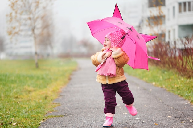 La bambina sotto un ombrello in autunno