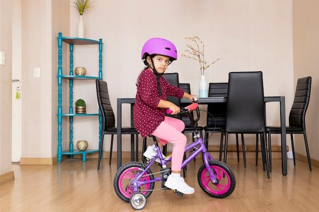La bambina sta andando in bicicletta nel suo salotto