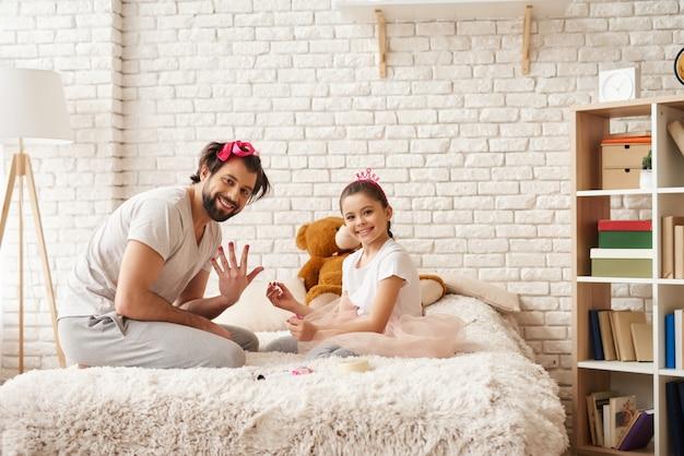 La bambina sta dipingendo i chiodi di papà con un polacco.