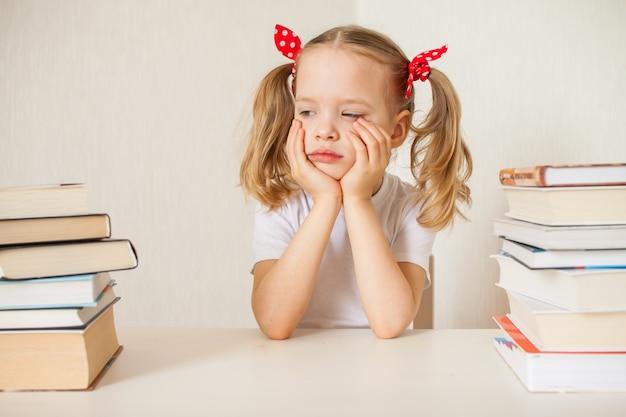 La bambina sta imparando le lezioni a casa. scuola a casa