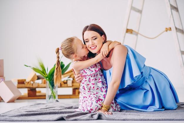 La bambina sveglia bacia la sua giovane bella madre con amore. mamma adorabile con sua figlia nella stanza decorata bianca.