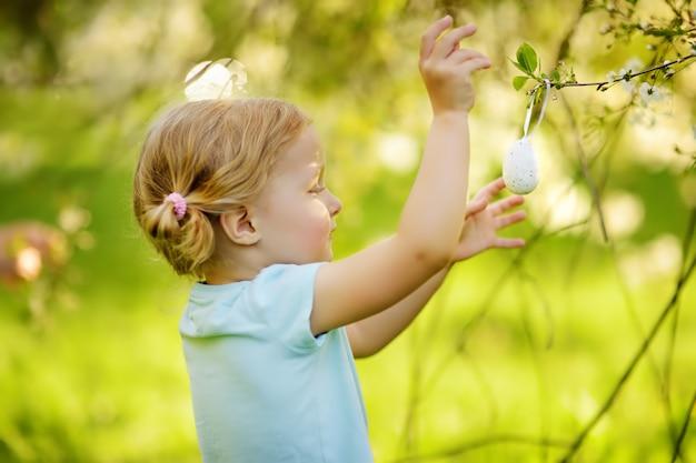 La bambina sveglia caccia per l'uovo di pasqua sull'albero di fioritura del ramo.