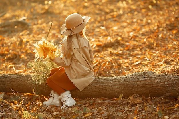 La bambina sveglia cammina in un parco di autunno