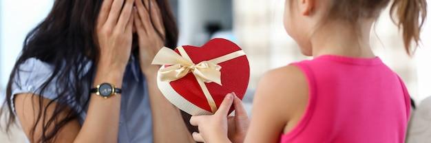 La bambina sveglia che dà al suo regalo di compleanno della mamma ha imballato in primo piano a forma di scatola rossa del cuore. stile di vita familiare dolce e concetto di felicità