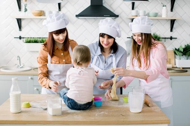 La bambina sveglia che si siede sulla tavola e la sue belle madre, zia e nonna in grembiuli stanno preparando la pasta per i muffin e stanno sorridendo mentre cuocevano nella cucina a casa. concetto di festa della mamma