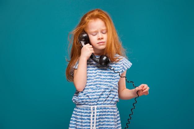 La bambina sveglia di bellezza in maglietta con capelli lunghi parla un telefono