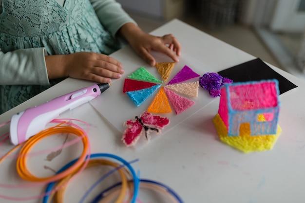 La bambina sveglia fa una casa di plastica con la penna 3d