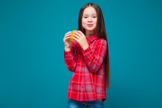 La bambina sveglia in camicia a quadretti con i capelli della brunetta tiene l'hamburger