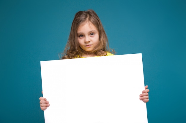 La bambina sveglia in maglietta con capelli marroni tiene la carta pulita