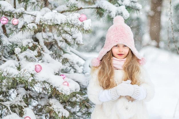 La bambina sveglia in una pelliccia bianca e la gonna lanuginosa rosa nella foresta nell'inverno veste l'albero di natale. giocattoli di natale rosa.