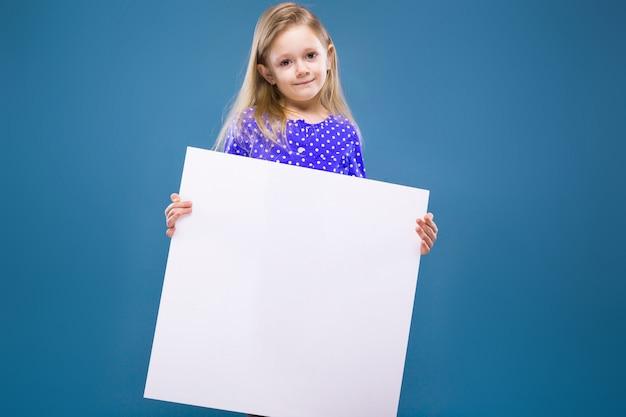 La bambina sveglia in vestito viola tiene il cartello in bianco vuoto