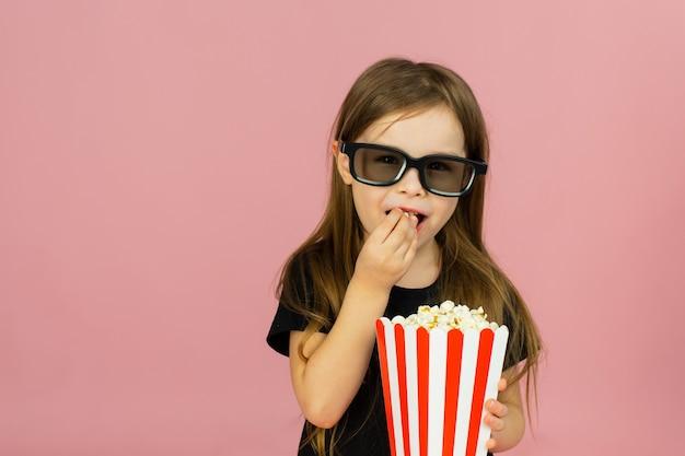 La bambina sveglia mangia popcorn da imballaggi a strisce e guarda un film con gli occhiali 3d. concetto di pubblicità cinematografica, guardare film online