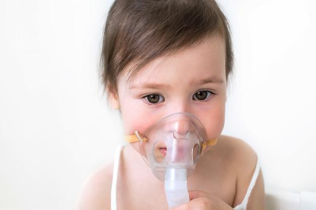 La bambina tratta la tosse e il naso che cola. la ragazza si siede con l'inalazione