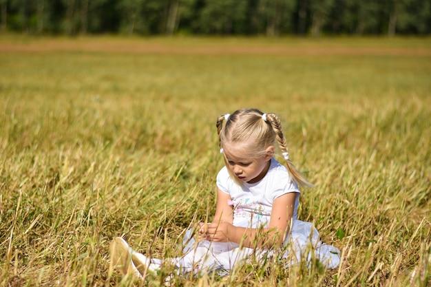 La bambina triste romantica in vestito bianco si siede sull'erba nel campo, guarda giù le mani