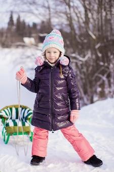 La bambina va in slitta in una calda giornata invernale