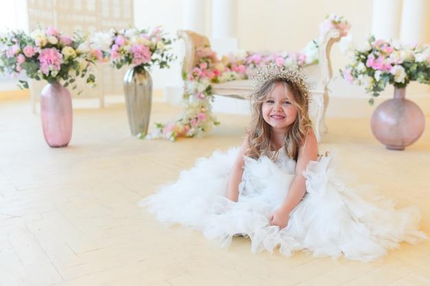 La bambina vestita come una principessa si siede tra i fiori nella stanza