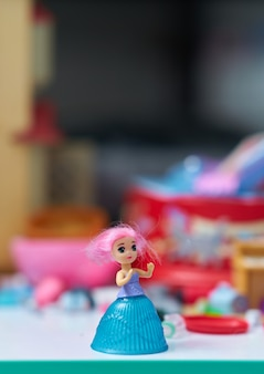 La bambola della ragazza sulla tavola sulla sfuocatura gioca il fondo