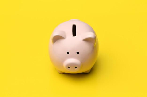 La banca piggy dentellare si leva in piedi nel centro su una priorità bassa gialla.