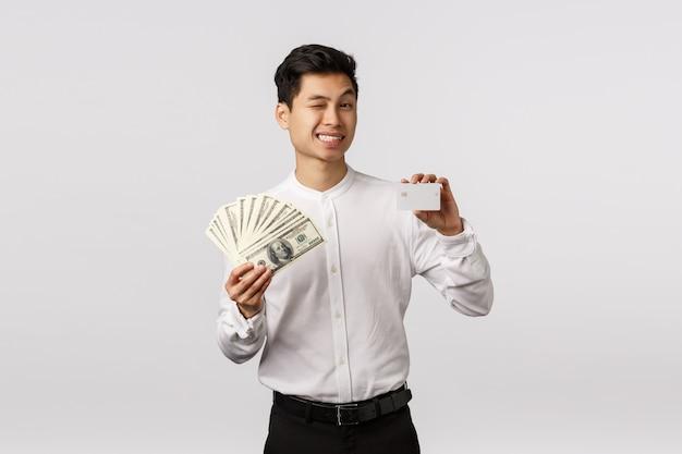 La banca rilassata ti ha coperto. sfacciato e rilassato, allegro imprenditore di successo asiatico ammiccante fotocamera e sorridente, mostrare soldi e carta di credito, consigli di mettere il deposito in contanti, in piedi