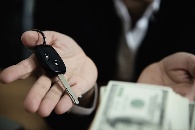 La banconota dei soldi di manifestazione dell'uomo di affari fa il piano finanziario invita la gente a vendere o comprare la casa e l'automobile - concetto di assicurazione di credito di prestito di proprietà monetarie