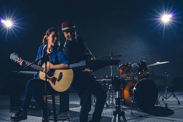 La band di due musicisti canta una canzone e suona uno strumento musicale con i musicisti del gruppo fellow