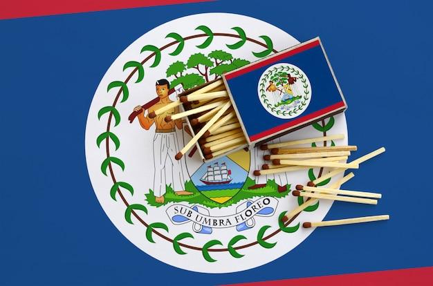 La bandiera del belize è mostrata su una scatola di fiammiferi aperta, dalla quale cadono diverse partite e si trova su una grande bandiera