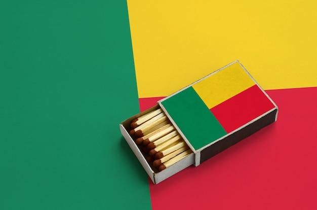 La bandiera del benin è mostrata in una scatola di fiammiferi aperta, che è piena di fiammiferi e si trova su una grande bandiera