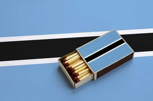 La bandiera del botswana è mostrata in una scatola di fiammiferi aperta, che è piena di fiammiferi e si trova su una grande bandiera