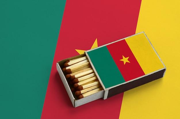 La bandiera del camerun è mostrata in una scatola di fiammiferi aperta, che è piena di fiammiferi e si trova su una grande bandiera