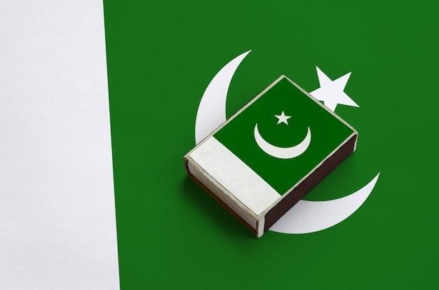 La bandiera del pakistan è raffigurata su una scatola di fiammiferi che si trova su una grande bandiera