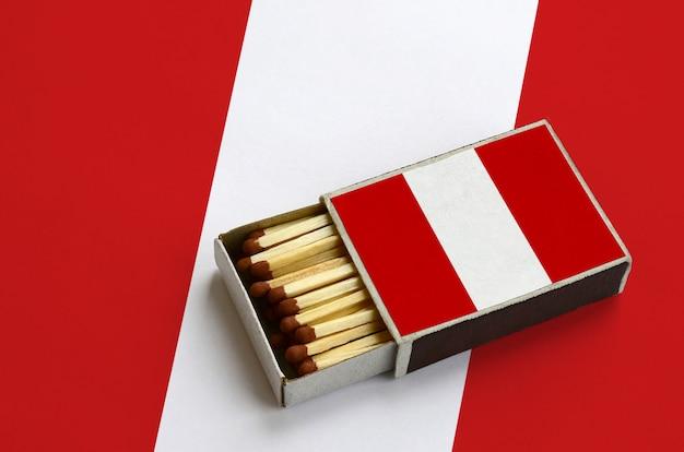 La bandiera del perù è mostrata in una scatola di fiammiferi aperta, che è piena di fiammiferi e si trova su una grande bandiera