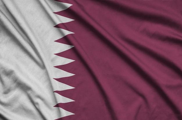 La bandiera del qatar è raffigurata su un tessuto sportivo con molte pieghe.