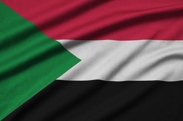 La bandiera del sudan è raffigurata su un tessuto sportivo con molte pieghe.